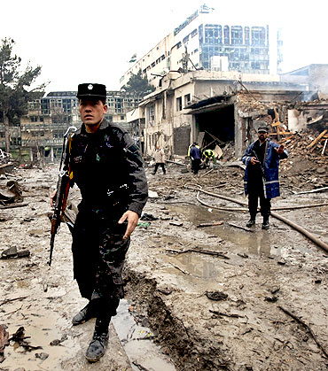 An Afghan policeman keeps watch at the site of the blast