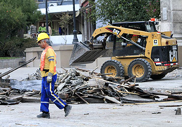 A municipal worker clears rubble from a street in Santiago after the quake.