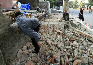 A man clears rubble after the quake in Santiago.