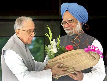 Jyoti Basu (L), hands a bouquet to Indian Prime Minister Manmohan Singh at his residence in Kolkata July 11, 2006