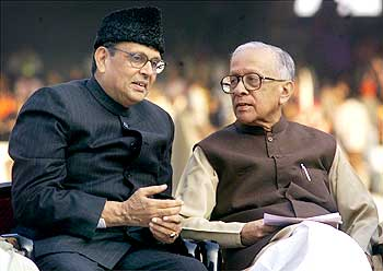 Former Indian prime minister V P Singh (L) speaks to veteran Marxist leader Jyoti Basu, after his retirement as chief minister in 2000