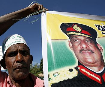 A member of the United National Party holds up a poster of former Sri Lankan army commander General Sarath Fonseka during a party convention in Colombo