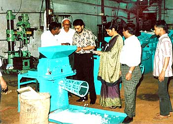 Dr Roy, accompanied by IFDC staff, observes a demonstration of a urea briquette machine at SIMS manufacturing company in Bangladesh