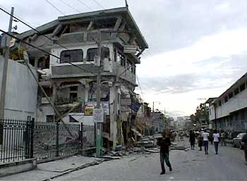 People walk along a street lined with buildings that were destroyed by the earthquake.