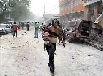 A woman carries a child after an earthquake in Port-au-Prince.