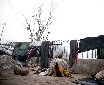 A homeless woman sits near a main road in New Delhi.