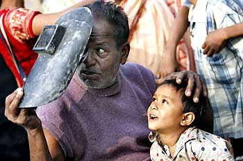 Villagers watch the annular eclipse of the sun through a welding mask at Harwood Point, south of Kolkata.