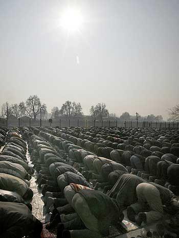 Kashmiri Muslim men perform special prayers during the annular solar eclipse in a park outside a mosque in Srinagar