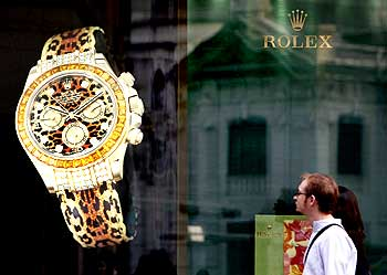 Foreign visitors walk past a watch brand advertisement at the Shinsegae department store in Seoul