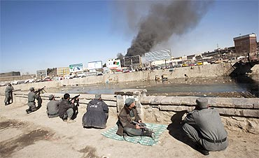 Afghan policemen take positions as smoke rises from a shopping mall