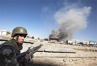 An Afghan National Army soldier takes position as smoke rises from a shopping mall