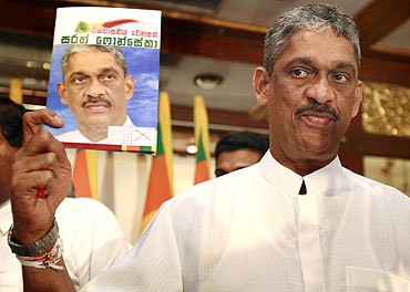 Presidential candidate Sarath Fonseka holds up a copy of his election manifesto