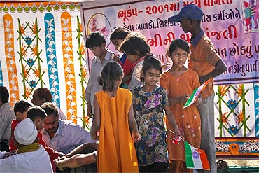Harilal Kapdi distributes flags and biscuits to children