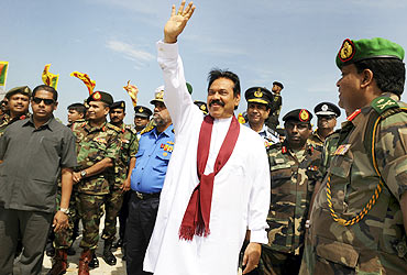 Rajapaksa waves during a photo opportunity with high-ranking military officials after unveiling a monument for fallen Sri Lankan soldiers
