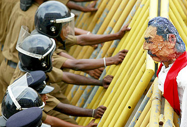 Police take up position behind a metal barrier as students from a group of universities hold a puppet of Rajapaksa over the barrier during a protest in Colombo