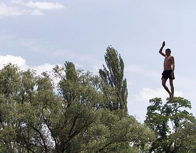 A man jumps into the cool water of the Dnipro river in Kiev. Ukraine has been experiencing very hot days this season.