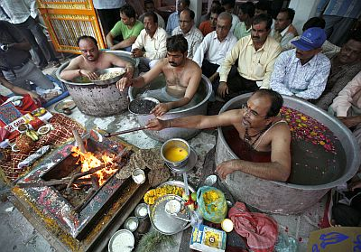 Priests sit inside cooking pots filled with water as they perform special prayers in order to appease Varun, the rain god, in the city of Ahmedabad in Gujarat on June 29, 2010.