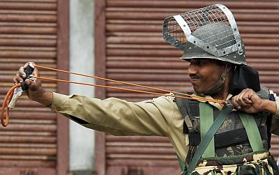 A policeman uses a sling shot during a Kashmiri protest against New Delhi's rule in the troubled Himalayan region of Kashmir, in Srinagar