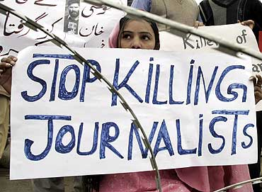 A man holds a placard during a protest against the killing of a journalist in Swat Valley