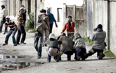 A Kashmiri protester throws stones towards policemen as foreign photographers take pictures