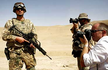 Photographers take pictures of an ISAF team during a drill near Kabul
