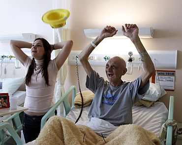 Brazilian patient Jorge Cocer and his daughter Carolina react during their national soccer team's 2010 World Cup Group G soccer match against Portugal, at the Cancer Institute Hospital in Sao Paulo.