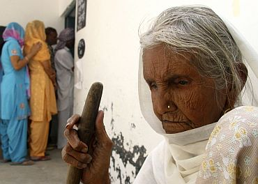 A woman waits to cast her ballot outside a polling station at Skatari village in Haryana