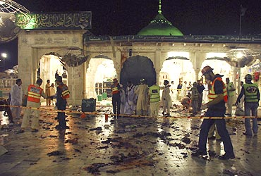 Rescue workers walk in the cordoned grounds of the Data Darbar shrine after it was hit by multiple suicide bomb attacks in Lahore