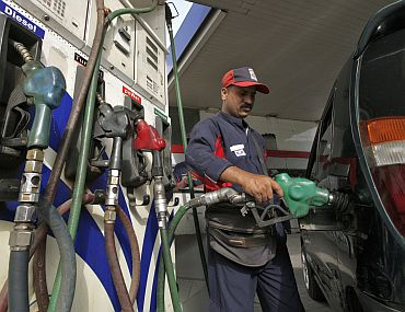 An employee fills a vehicle with petrol at a fuel station in New Delhi on June 25