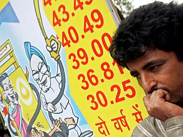 A Bharatiya Janata Party activist stands near a placard, which depicts the increase in petrol prices