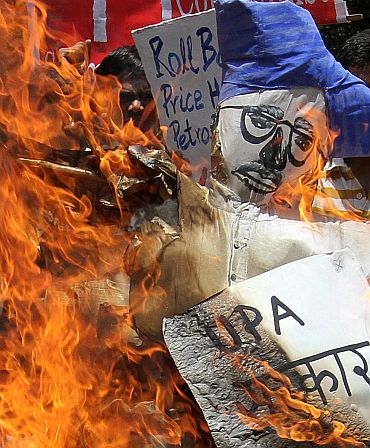 Activists from the Socialist Unity Centre of India burn an effigy of Prime Minister Manmohan Singh