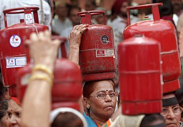 BJP activists hold LPG cylinders during a protest in New Delhi