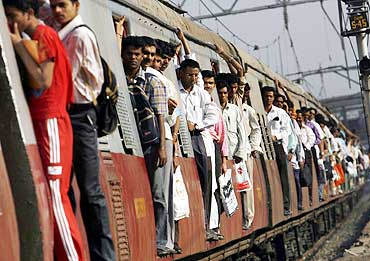 Commuters travel in a suburban train in Mumbai