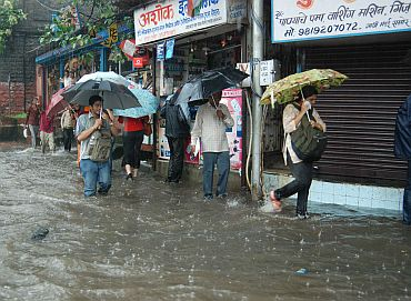 People wade through a waterlogged street near Dadar