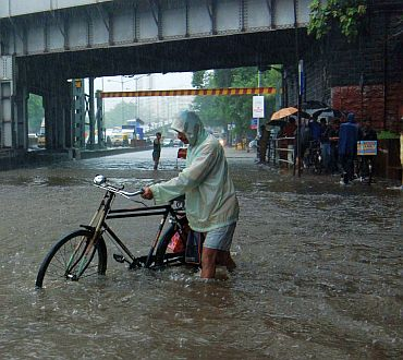 A cyclist finds his way through a waterlogged street at Hindmata