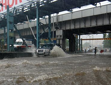 An SUV wades through a flooded road in Hindmata