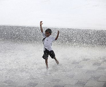 A boy enjoys himselfs as huge waves hit Mumbai's seafront during high tide