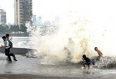 Children enjoy the waves at Worli seaface in Mumbai on a rainy day