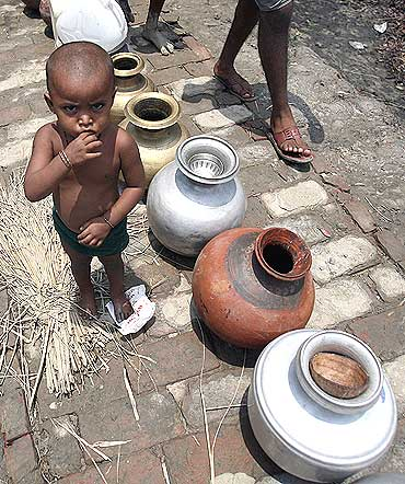 A child waits for water from a non-governmental organisation