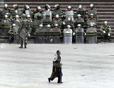 A Tibetan man walks past soldiers in the main square in Kangding city, China