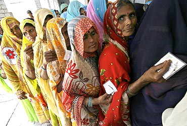 Voters wait outside a polling station in Rohania, Uttar Pradesh