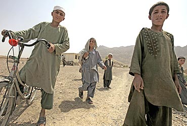 Afghan boys watch a US patrol team in Arghandab District, north of Kandahar