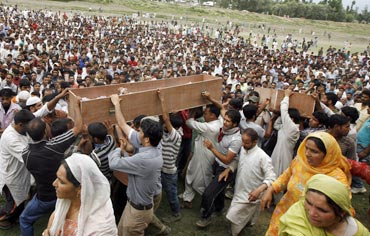 Kashmiri people carry the bodies of two youths after funeral prayers in Srinagar on July 6