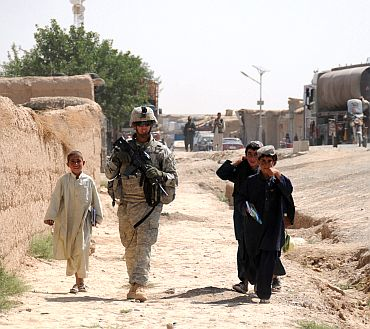 Afghan children walk alongside a US army soldier during a patrol in Zabul province, Afghanistan