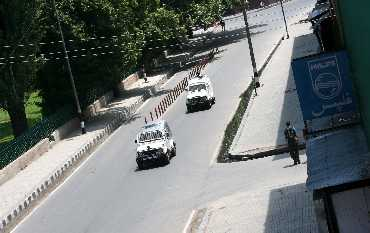 Army vehicles pass through a deserted road in Srinagar