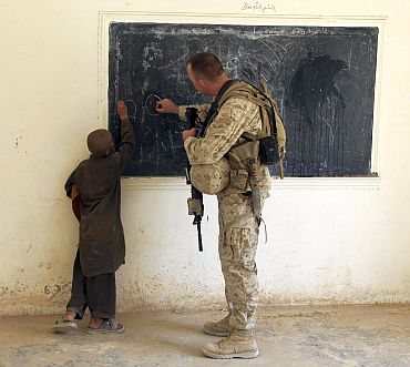 A US Marine writes on a chalkboard with an Afghan boy during a renovation planning visit at a school in the Nawa district of the Helmand province of Afghanistan