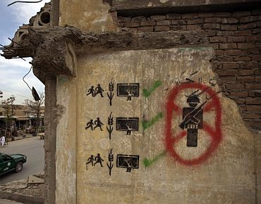 Graffiti on a demolished building as a police vehicle drives on the road in Kabul