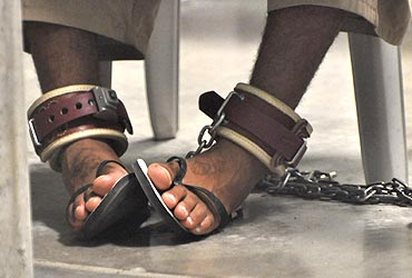 A Guantanamo detainee's feet shackled to the floor as he attends a 'Life Skills' class
