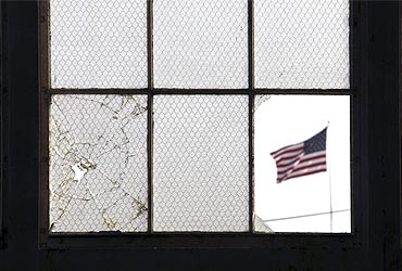 An Amercian flag flutters, when seen from a broken window from inside an unused airplane hangar in Guantanamo Bay