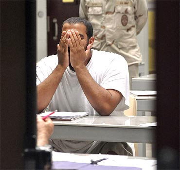 A Guantanamo detainee rubs his face while attending a 'Life Skills' class inside the camp